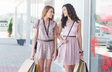 Outdoor shot of two smiling Caucasian women shopping together.
